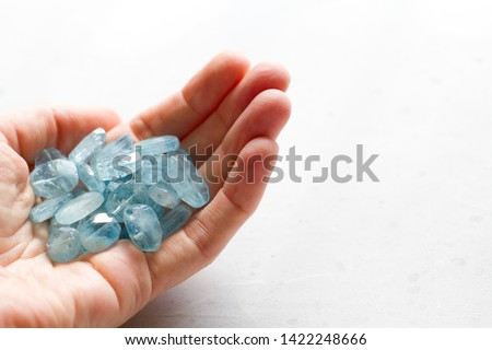 Aquamarine stone lies in the hand. Natural stone Aquamarine on a white background. Female hand. Copy space for your text. #1422248666
