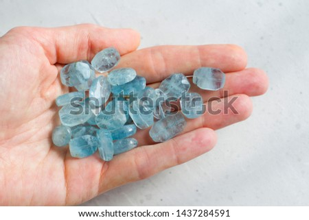 Aquamarine stone lies in the hand. Natural stone Aquamarine on a white background. Female hand. Copy space for your text. #1437284591
