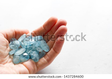 Aquamarine stone lies in the hand. Natural stone Aquamarine on a white background. Female hand. Copy space for your text. #1437284600