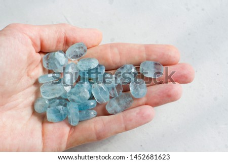 Aquamarine stone lies in the hand. Natural stone Aquamarine on a white background. Female hand. Copy space for your text. #1452681623