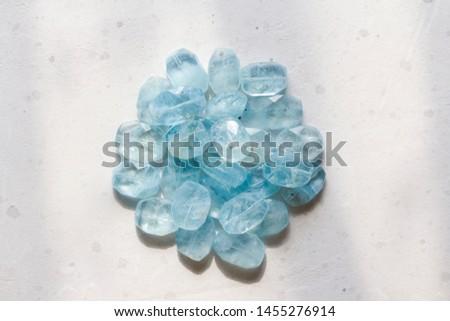 Aquamarine stone. Natural stone and aquamarine crystals on a white background. Beautiful aquamarine stones. #1455276914