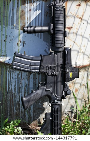 AR-15 M4A1 .223 caliber assault carbine with holographic sight (collimator). Old barrel in the background. #144317791