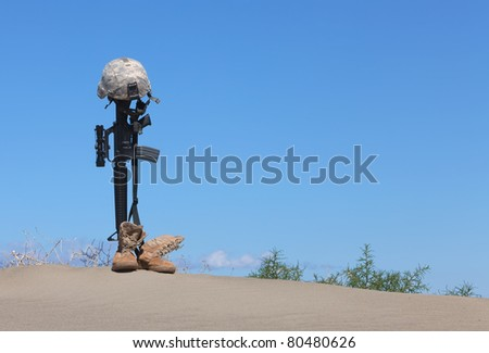 AR-15 rifle with combat helmet and boots as a memorial to a fallen soldier.