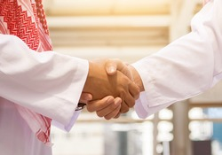 Arab and businessman are shaking hand on cityscape background, Business Successful concept
