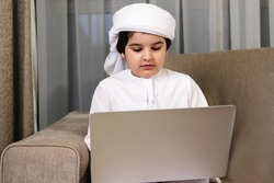 Arab boy home school using laptop computer. Arabic Emirati student on video conference while homeschooling ideal for Education campaign. Middle East kid Kandura dish dash