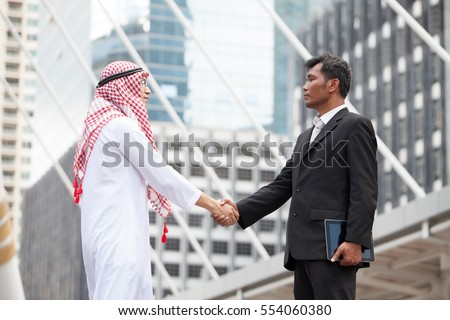 Arab Business partners handshaking and american business people after a successful business deal on city background in Thailand. Adhering to respect commitment and integrity in business.