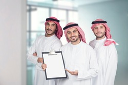 Arab business people in a meeting, three business people standing in a modern office holding a folder for presentation, ethnic business people, business team.