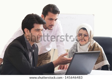 Arab business woman in a meeting with colleagues, three business people in the meeting, ethnic business people, business team.