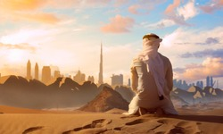 Arab Emirati man praying on top of a dune in UAE desert front Dubai skyline.