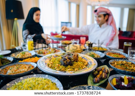 Arab family in traditional clothes eating during the holy month of Ramadan at Iftar.Feast in honor of Eid Mubarak. The family sits on the background of a table filled with traditional food Eid Al Adha