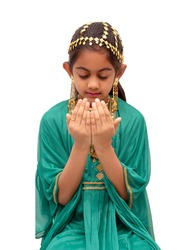 Arab girl dressed up for Eid festival wearing a traditional arabic green dress with gold ear ring, head and neck jewellery and praying with folded hands.