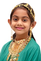 Arab girl dressed up for Eid festival wearing a traditional arabic green dress with gold ear ring, head and neck jewellery.