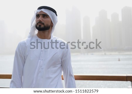 Arab male model looking up wearing Emirati dress and ghutra turban with copy space background