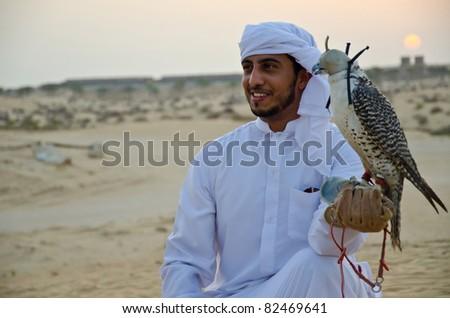 Arab man carrying wild falcon