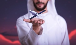 Arab Man holding floating Orbiter or Spacecraft on hand, UAE to Mars, Arabic Space discovery.