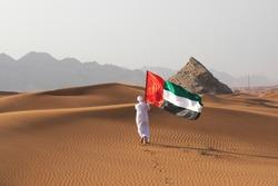 Arab man holding the UAE flag in the desert celebrating UAE national day and Uae flag day.