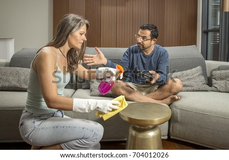 arab man playing a video game while woman is cleaning around him in their city apartment