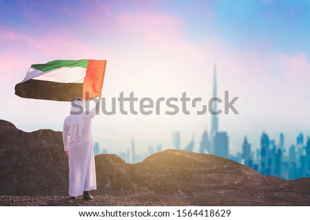 Arab man rising UAE flag standing front dubai skyline