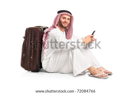 Arab man sitting near a suitcase and typing a text message on his cellphone isolated on white background