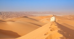 Arab man sitting on top of a dune in arabian desert