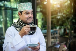 Arab man standing and drinking black coffee.
