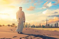 Arab man standing front Dubai skyline in the desert of UAE