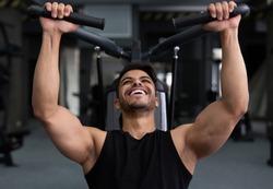 Arab man training hard at gym, doing workout on fitness machine