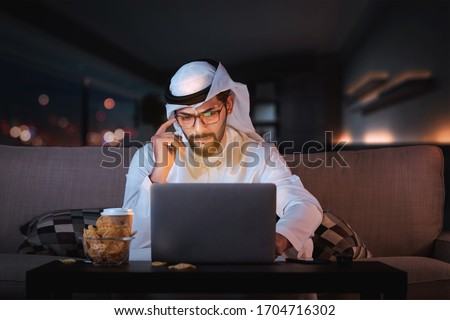 Arab man working from home sitting on sofa late at night time. coronavirus Quarantine.