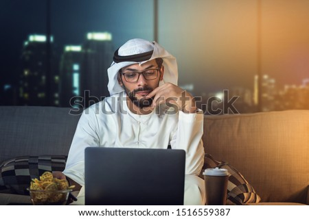Arab man working late from home sitting on sofa night time