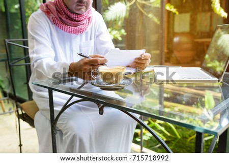 Arab muslim business man ware white traditional clothing and hold paper in hand,On table have laptop smartphone and cup of coffee #715718992