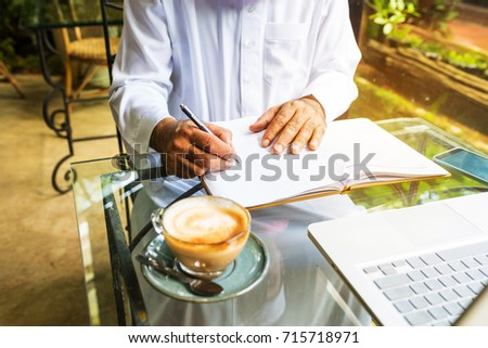 Arab muslim business man ware white traditional clothing and write on paper ,On table have laptop smartphone and cup of coffee #715718971