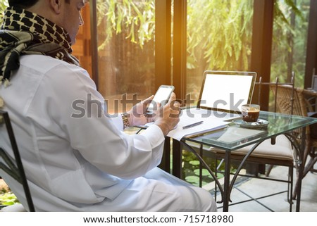 Arab muslim business man ware white traditional clothing in hand use smart phone and open laptop on coffee glass table #715718980