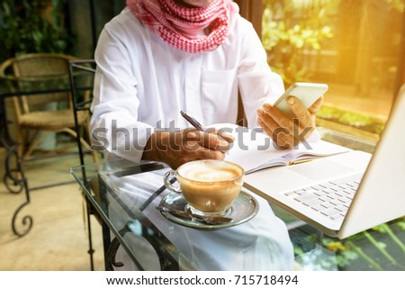 Arab muslim business man ware white traditional clothing in hand writing something on paper and look at smart phone with laptop on coffee glass table #715718494