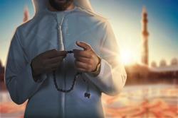 Arab Muslim man holding islamic rosary, standing inside a big mosque. ramadan Kareem Islam religion, holy month.