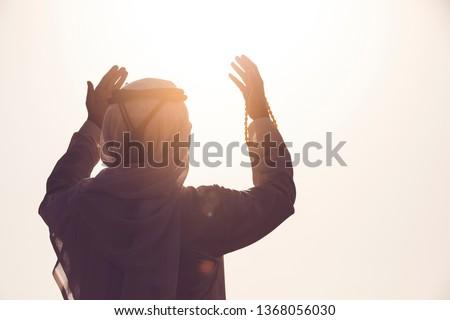 Arab Muslim man pray and doing Duaa under sunrise light, Islamic religion and Ramadan Kareem concept.  #1368056030