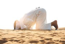 Arab Muslim man wearing Kandura, and  pray in the desert on the sand, Islamic concept - Ramadan Kareem.