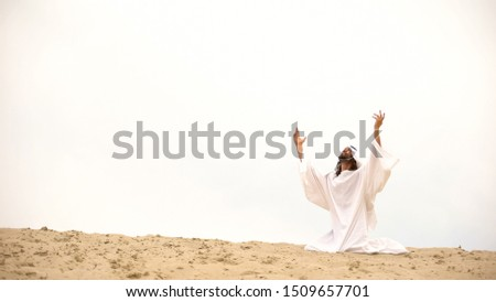 Arab raising hands to heaven, praying on knees, asking Allah to forgive sins