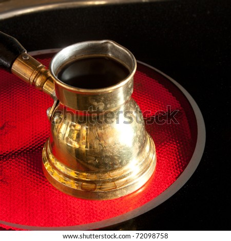 Arab small coffee pot on red hot ceramic stove of electric cooker