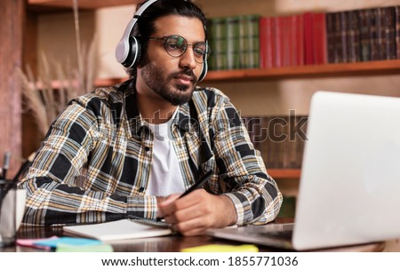 Arab Student Guy Learning Online At Laptop Computer Studying Sitting In Library Near Bookshelf In University. Modern Education, E-Learning And Online Training Concept. Selective Focus