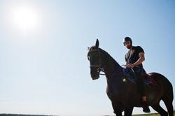 Arab tall beard man wear in black helmet, ride arabian horse.