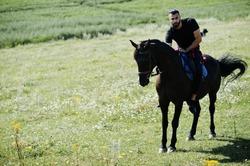 Arab tall beard man wear in black ride arabian horse.