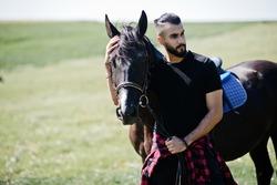 Arab tall beard man wear in black with arabian horse.
