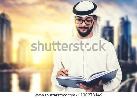 Arab teacher, professor, student writing at his notebook, in dubai, uae background