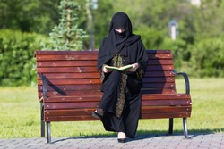 Arab woman in black national dress is reading a book in a city park A migrant from the Middle East is sitting on a bench.