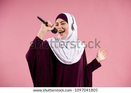 Arab woman in headphones sings karaoke. Isolated on pink background. Studio portrait. #1097041805