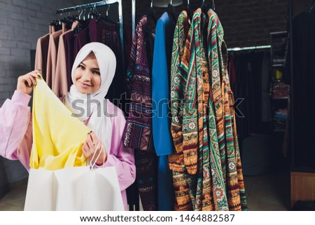 Arab woman in traditional Muslim clothes buys a new dress in an Oriental store. #1464882587