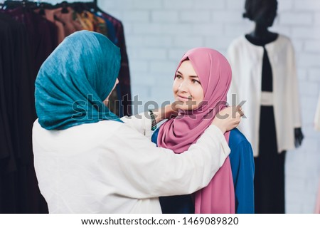 Arab woman in traditional Muslim clothes buys a new dress in an Oriental store.