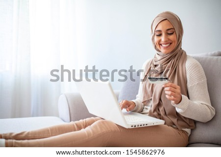 Arab woman making online purchase on laptop. Portrait of happy woman purchasing product via online shopping. Pay using credit card. Muslim woman online shopping