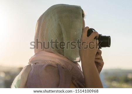 Photo of Arab Woman Photographer in a scarf taking picture using Camera on the sunset background. Halal travel concept