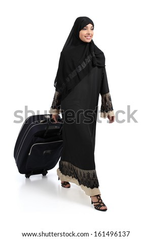 Arab woman walking carrying a suitcase isolated on a white background
